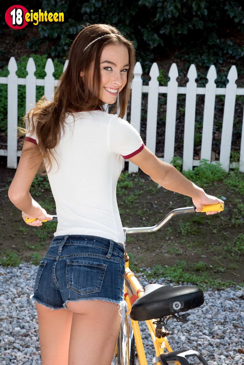 Девушка на велосипеде позирует без трусов около белого забора
