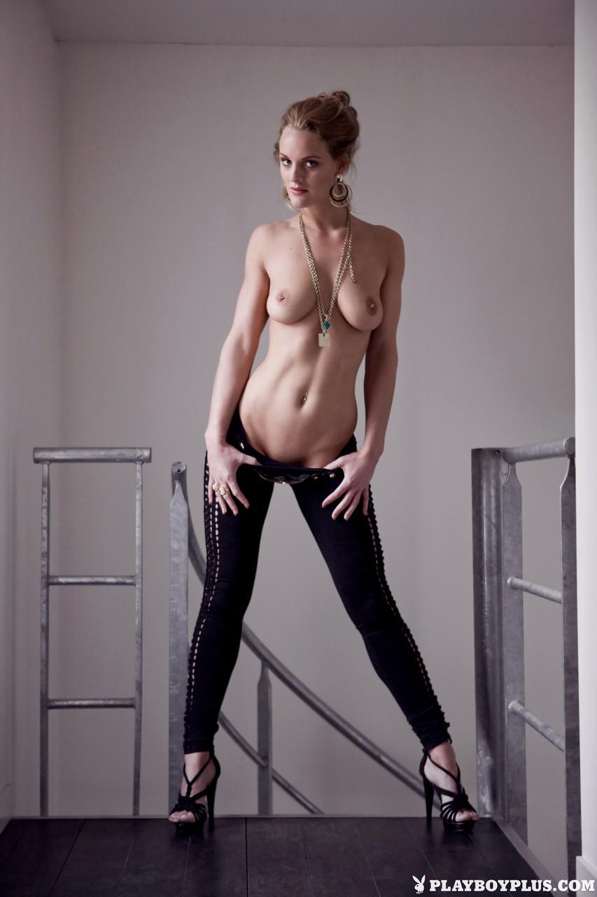 Милфа со стоячими сиськами в черных туфлях обнажается в камеру фотографа