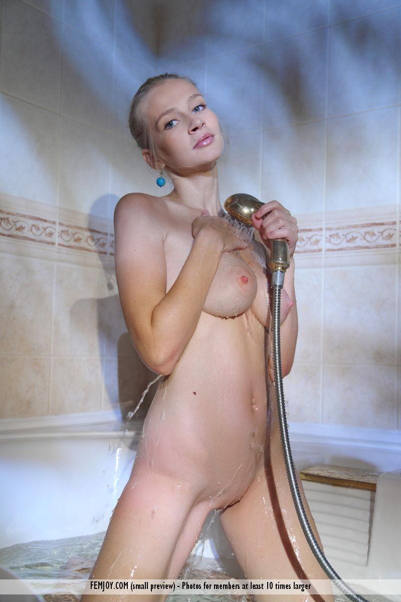 Худая с голубыми сережками позирует нагишом в ванне и возбуждается