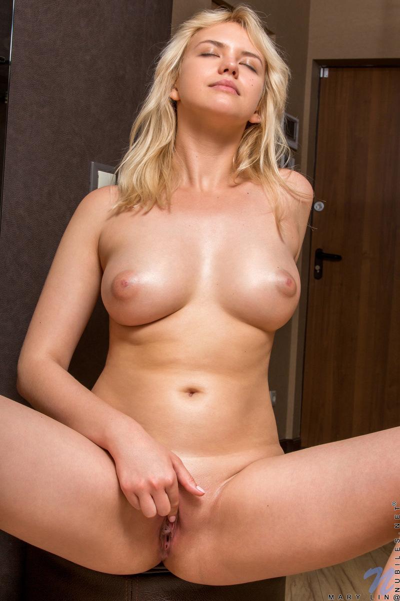 Сисястая блонди с острыми сосками на полу комнаты дрочит рукой влагалище
