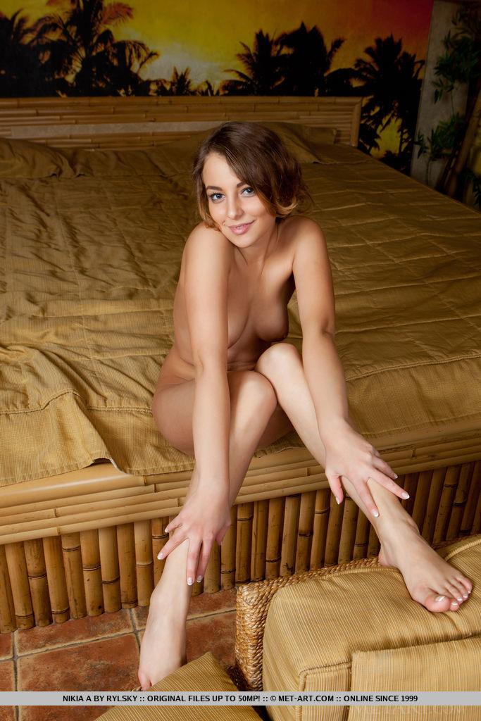 Девка с пирсингом пупка на бежевом диване играет с мокрой вагиной