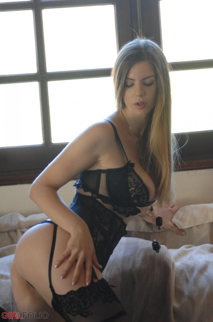 Красавица в корсете и чулках делает на краю диване интимные фото