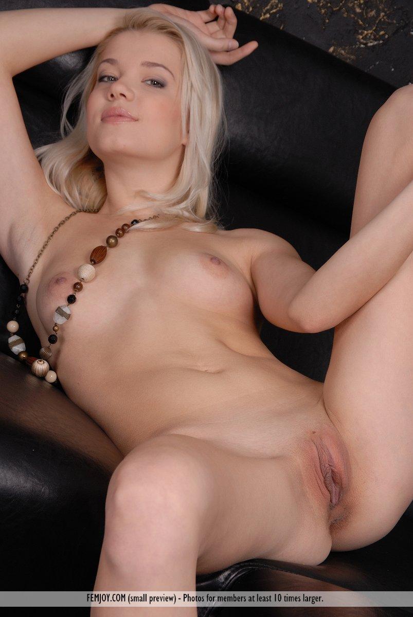 Красавица на черном кожаном диване показала большие половые губки